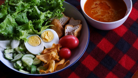 Muslim salad with sauce on wood table and have some space for write wording, delicious appetizer with many kinds of vegetable, green leaf lettuce, onion, boiled egg, tofu, high nutrition