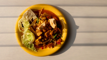Papaya salad with sweet corn and salted egg in yellow dish on table in sunlight and have space for write wording, very popular fusion Thai north eastern street food for fat people and general tourist Фото со стока