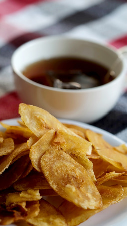 Sweet crispy banana chips serve with hot tea on white dish and thai style cloth with space for write wording, a way to preserve agriculture fruit and adding value to growth business export worldwide.
