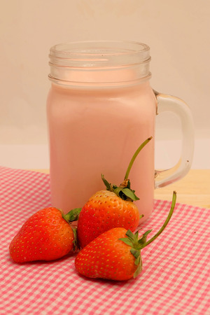 Strawberry and milk strawberry flavor on wood table and space for write wording, sweet romantic fruit for special person in Valentine day, make many dessert menu or juice or dairy strawberry flavor