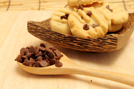 Chocolate chip butter cookie in wood bowl on wood table and space for write wording, delicious snack or dessert, cookie, cake, served with coffee or tea for special celebration or party Stock Photo