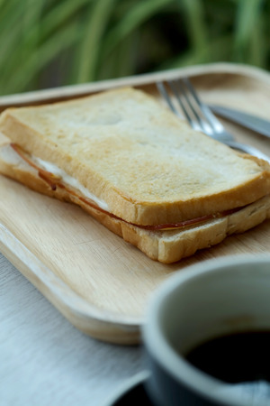 Ham cheese sandwich on wood tray and space for write wording, easy delicious food served with coffee or tea in coffee shop or office, suitable for new working life that need more time to work 版權商用圖片