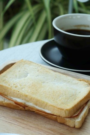 Ham cheese sandwich on wood tray and space for write wording, easy delicious food served with coffee or tea in coffee shop or office, suitable for new working life that need more time to work Stock Photo