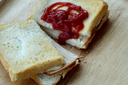 Ham cheese sandwich, tomato ketchup and chili sauce on wood tray and space for write wording, easy delicious food served with coffee or tea in coffee shop or office, popular food for office worker