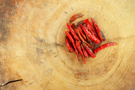 Flat lay of dry chili on wood cutting board, main ingredient of making Thai spice food by blending and mixed with others herb and put in curry for spice taste and good smell, have space for write wording