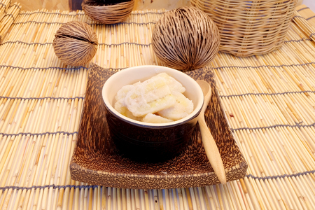 Banana in coconut milk, popular dessert from fruit, Thai style home made dessert in a cup on wood mat served after meal or appetizer, popular street food of Thailand, have space for write wording