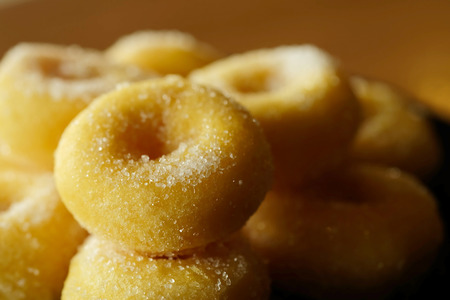 Fried donut with sugar, popular sweet  sold in market or restaurant, high calories, sugar and cholesterol level cause of many chronic disease such as diabetes and heart disease affect economic problem Stock Photo