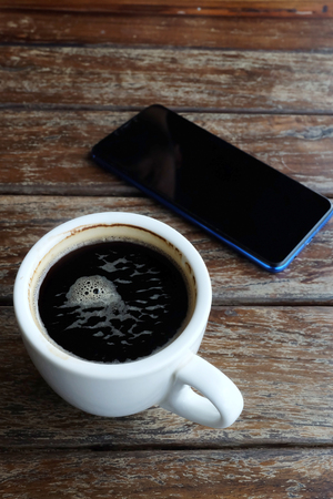 Flat lay photo of smartphone and black coffee on wood table with space for write wording, innovation that change the world such as communication way, business strategies, marketing strategies