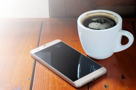 photo of smartphone and black coffee on wood table with space for write wording, innovation that change the world such as communication way, business strategies, marketing strategies  Photo of smartphone and black coffee on wood table with space for write wording, innovation that change the world such as communication way, business strategies, marketing strategies
