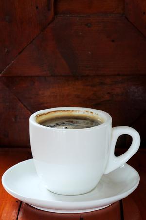 Café noir chaud bien mélangé dans une tasse à café blanche avec espace pour écrire le texte servi dans un restaurant à l'heure de la pause-café, boisson populaire pour le lieu de rencontre et la fête, conception à valeur ajoutée pour de meilleures ventes