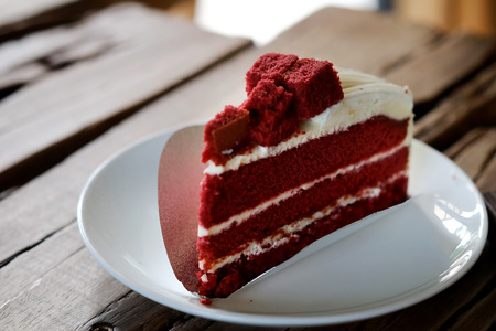 Red velvet cheese cake in a white dish on wood table in a garden style coffee shop with space for write wording, good choice for eating with coffee or tea with friends or lovers