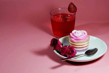 Multilayer sweet coconut fruit jelly with beverage, strawberry and red roses on white plate and pink background and space for write wording for happiness moment. Unhealthy dessert high sugar and fat. Reklamní fotografie - 129375050