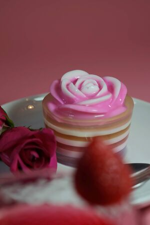 Multilayer sweet coconut fruit jelly with beverage, strawberry and red roses on white plate and pink background and space for write wording for happiness moment. Unhealthy dessert high sugar and fat. Reklamní fotografie - 129375056