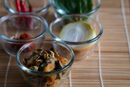Set of important ingredients for making Stir Fried Mussels with Thai Basil and Chili on wood mat and space for write wording containing Mussels, Onion, Red Chili Paste, Chili and Thai Basil leaves