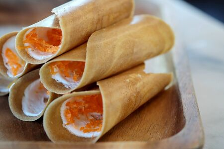 Thai crispy pancake on wood plate with space for write wording , popular sweet street snack sold in market and restaurant, unhealthy food contain high sugar, fat and fat cause of many chronic diseases 스톡 콘텐츠