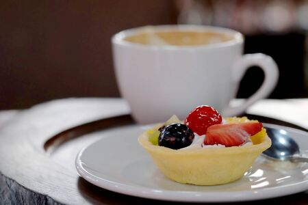 Mix fruit tart on white dish and hot coffee served on wood trey in a restaurant, famous refreshment and sweet for meeting place and restaurant. High sugar affect health problem such as Diabetes