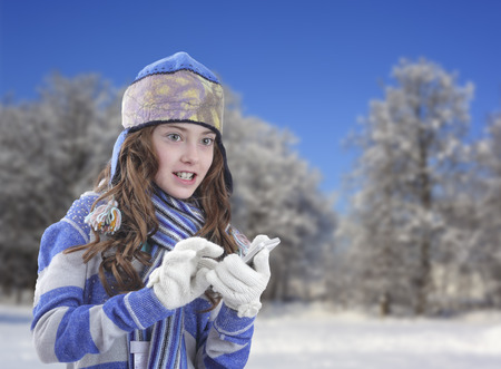 Girl in winter clothing with smartphone photo