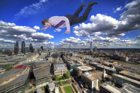 topple: Businessman falling down with modern city in background