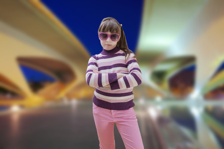nite: Teenage girl in pink wears sunglasses with modern city in background Stock Photo