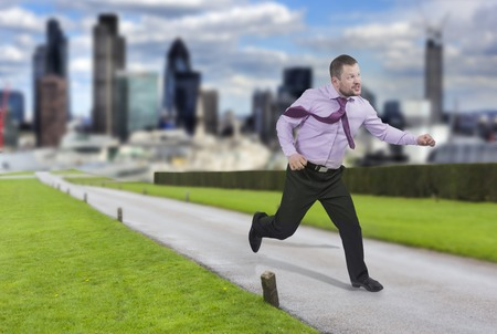 lateness: Running businessman in a hurry with modern city in background