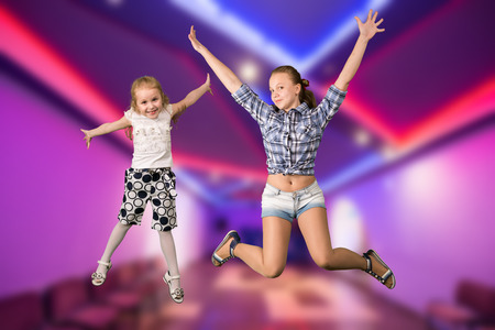 Two girls jumping in dancing hall interior