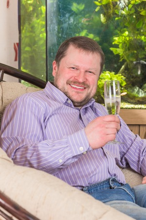 champaign: Man sitting in armchair with glass of champaign with aquarium on background