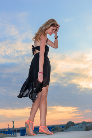 long sexy legs: Beautiful woman standing on blue sky sunset background