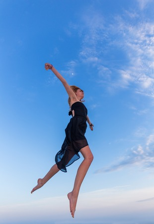long sexy legs: Young beautiful woman jumping on blue sky background