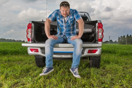 car trunk: Solid man sitting on car trunk on natural background Stock Photo