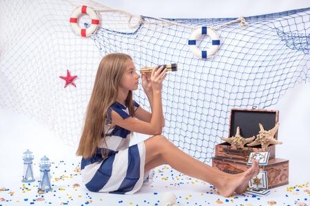 ocean fishing: Beautiful teen girl in blue and white dress looking in telescope Stock Photo