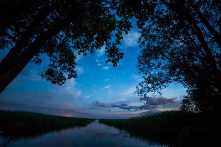 river shore landscape trees sky night view Standard-Bild