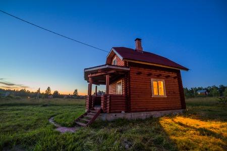houten huis buitenkant met lichten nacht uitzicht Stockfoto