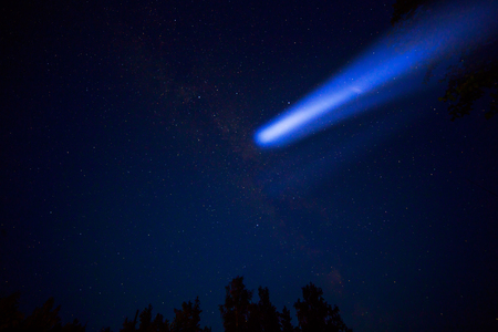 Comet in night sky and trees on background