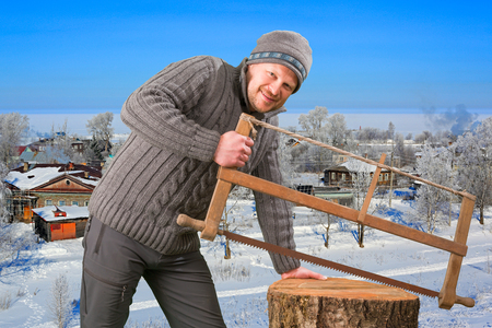 winter wood: Man with saw collecting firewood in winter outdoor Stock Photo