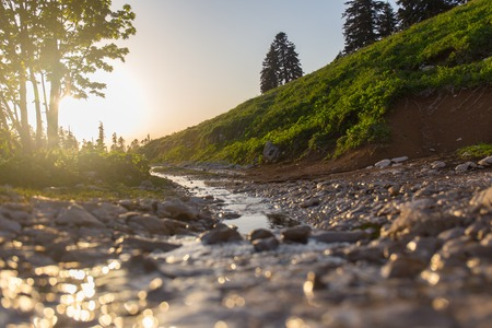 Highlands stream in rays of light mountain river Stock Photo
