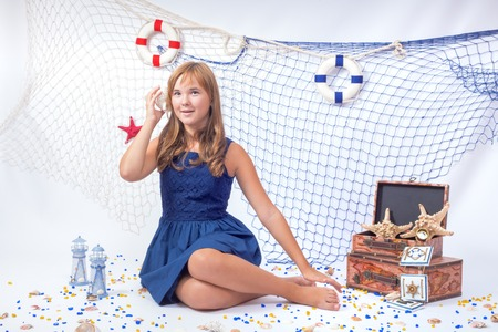 teen girl: Beautiful teen girl listening sea shell with fishing net in background