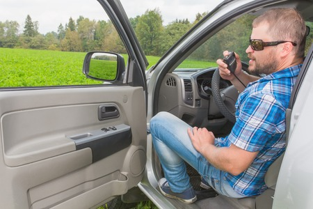 transceiver: Man sitting in a car on drivers place and talking handheld transceiver Stock Photo