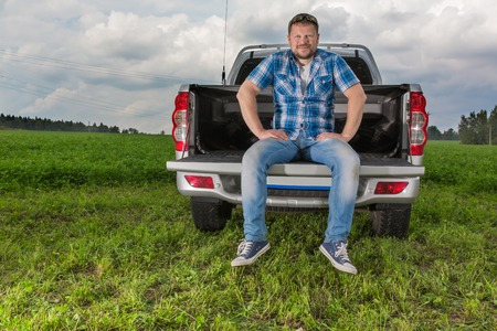 car trunk: Solid man sitting on car trunk natural background