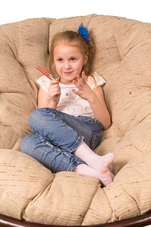 gir: Little gir with lipstickl sitting in armchair with lipstick Stock Photo