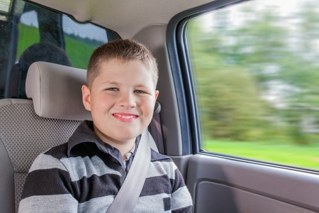 boy sitting: Teenager sitting in a car in safety chair fasten by seat belt