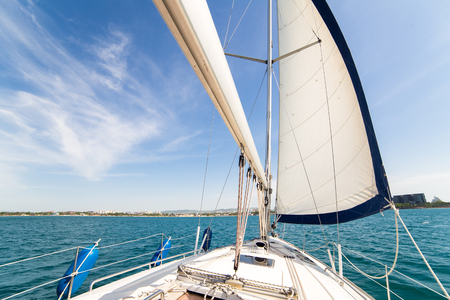 sailing ships: Yatch sail and desk on blue sky and sea background