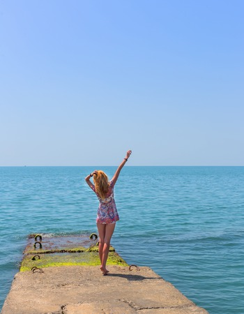 staying: Attractive young woman staying on the pier