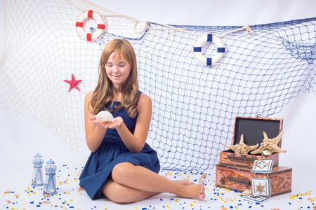 beautiful teen: Beautiful teen girl looking at seashell with fishing net Stock Photo