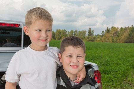 car trunk: Two boys siiting on a car trunk on natural background