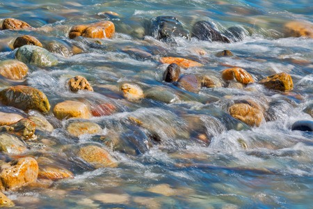 Pebble stones in the river water close up view, natural background Banco de Imagens