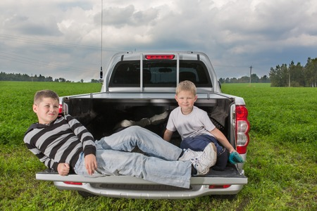 car trunk: Two brothers siiting on a car trunk on natural background