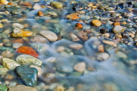 Pebble stones in the river water close up view, natural background 写真素材
