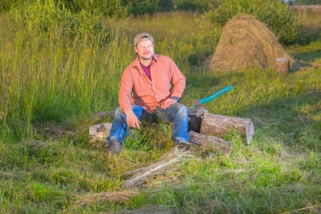 haystack: Farmer with an axe sitting near haystack