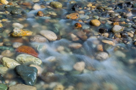 Pebble stones in the river water close up view, natural background Imagens