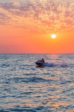 Man riding jet ski on colorful sunset over the sea